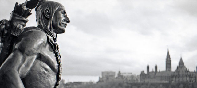 bronze statue of traditionally dressed Aboriginal man with braids with Canada's Parliament Buildings in background